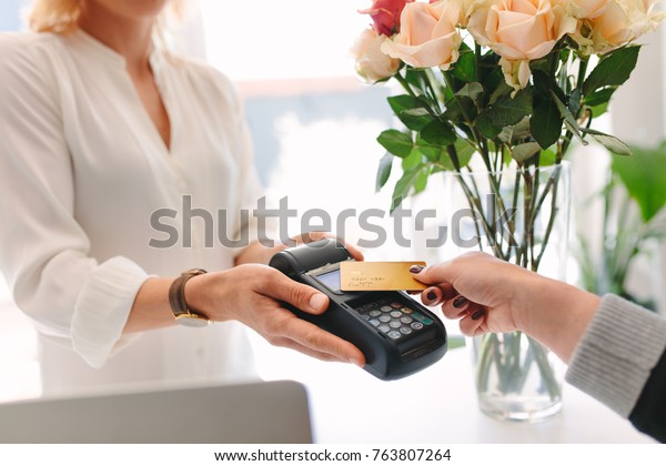 Hand des Kunden, der Zahlung durch nfc Technologie Kreditkarte im Blumenladen. Kunde zahlt mit kontaktloser Karte bei Florist
