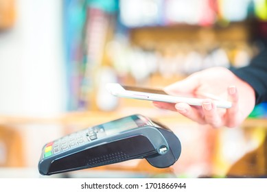 Hand of customer paying with contactless by mobile device. Payment with mobile.