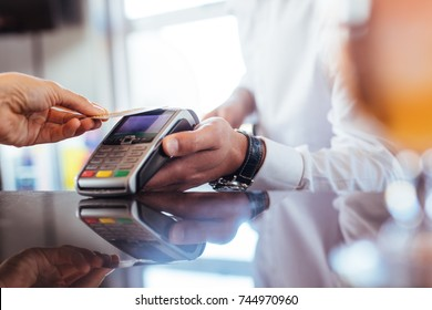 Hand of customer paying with contactless credit card with NFC technology. Bartender with a credit card reader machine at bar counter with female holding credit card. Focus on hands.