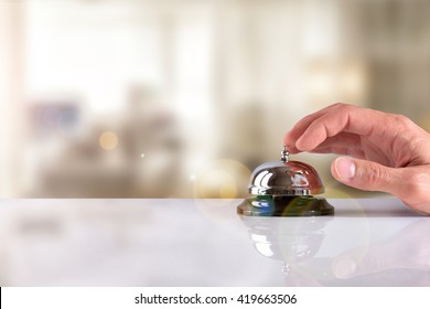 Hand of a Customer ringing the bell hotel service on a table white glass. Concept hotel, travel, room. Front view