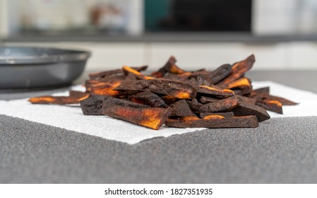 Hand cut, overcooked, potato fries tipped in a pile on white kitchen towel. The chips are blackened, crispy and unappetising. A grey work surface, frying pan and white home kitchen in shallow focus.