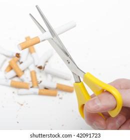 A hand cutting cigarettes
