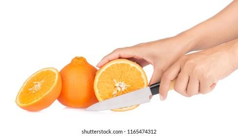 Hand cutting orange fruit with Knife isolated on white background