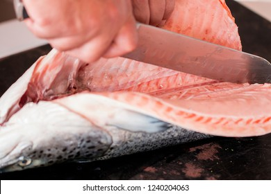 A hand cutting a raw salmon with a knife.