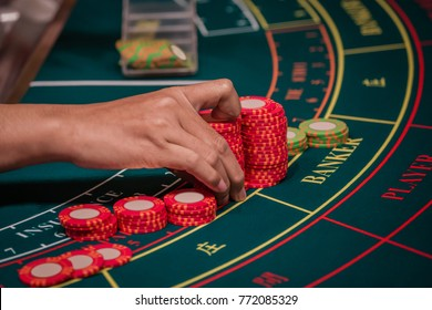A Hand of Dealer Organizing the Red and Green Baccarat Chips on Baccarat Gaming table.