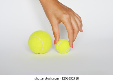 Hand of an debutant athlete choosing a small tennis ball on white background
