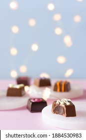 Hand decorated chocolate candy bonbons and pralines desserts on pink and blue background with lights bokeh