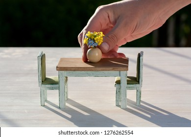 A hand decorating a wooden dining table with flowers in a vase, doll house furniture, home decoration or flower arrangement concept