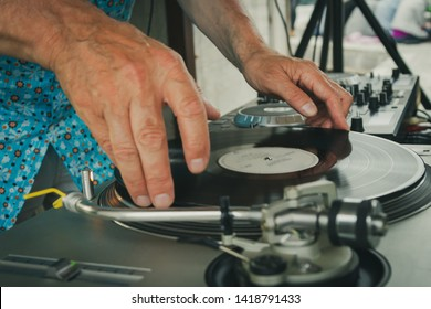 Hand of a deejay putting a vinyl record on a record player in a music club with vintage look.