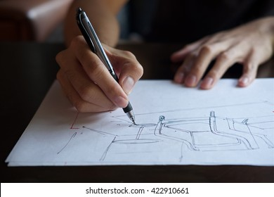 The hand of the designer with a pen, designing and sketching a furniture product