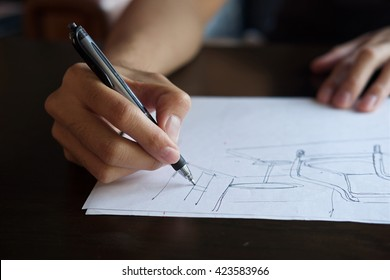 Hand of Designer with a pen, designing and sketching his idea