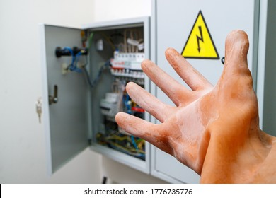a hand in a dielectric glove reaches for the electrical panel. compliance with labor protection rules when working in electrical installations