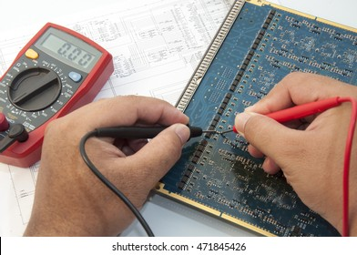 Hand with digital multimeter probes above board with components. Repair of Electronics circuit board.