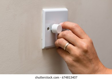 Hand dimming the lights to save on consumption and energy