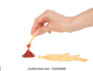 Hand dip french fries chips into ketchup on a white background