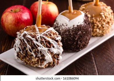 Hand dipped caramel covered apples decorated with nuts and chocolate sitting on white plate