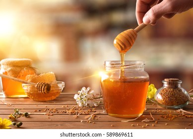 Hand with dipper picking honey from a jar of honey. Jars of honey, bee honeycomb and bee pollen on wooden table with flowers in a rustic kitchen and sunbeam. Front view. Horizontal composition
