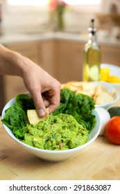 Hand dipping chip into a fresh delicious bowl of handmade guacamole with ingredients nearby