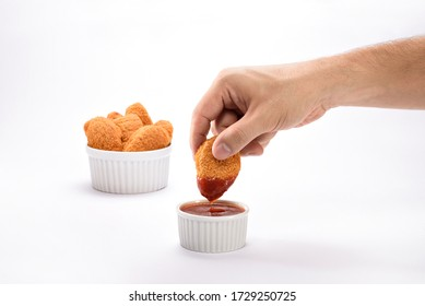 A hand dipping a delicious and crispy orange chicken nuggets on a ketchup sauce, isolated on white background, with a portion of nuggets served on a ramekin on the background.