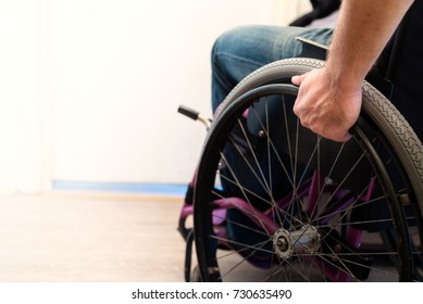 Hand of disabled paraplegic man in sitting wheelchair pushing wheel to ride indoor, disability concept