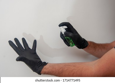 Hand disinfection by sanitizer. Humans hands in black nitrile gloves.