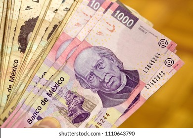 Hand displaying a stack of seventy thousand Mexican pesos. Obverse side of Mexican 1000 peso MXN banknotes with the image of Miguel Hidalgo y Costilla, horizontal view.