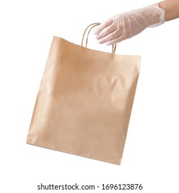A hand in a disposable medical glove holds a paper craft package with goods. Isolated object on white, safe delivery in compliance with sanitary standards.