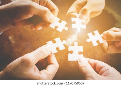 Hand of diverse people connecting jigsaw puzzle. Concept of partnership and teamwork in business
