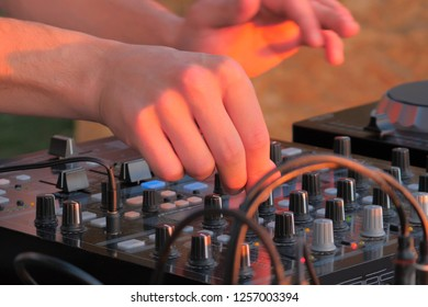 Hand of DJ controlling turntable console mixer. DJ playing music outdoor. Close up