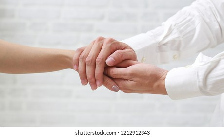 Hand of doctor reassuring her female patient.