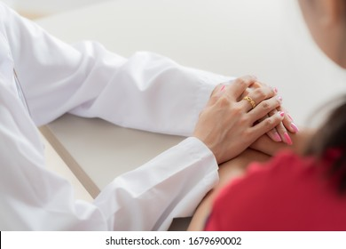 Hand of doctor reassuring her female patient. Asian people