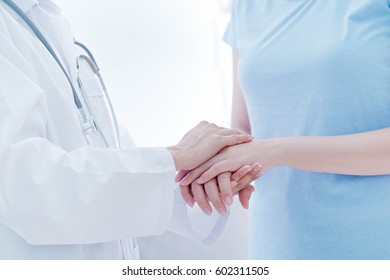 Hand of doctor reassuring her female patient