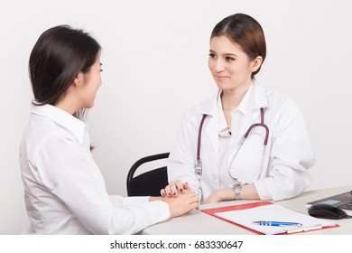 Hand of doctor reassuring her female patient in the consulting room.