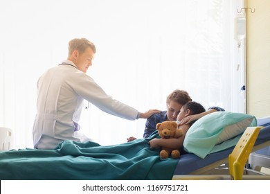Hand of doctor reassuring Patient family with child patient on hospital bed at the Patient room in hospital / Medical healthcare concept.