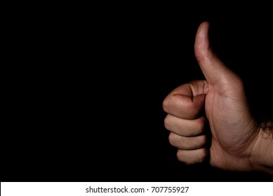 Hand doing an approval sign on a black background