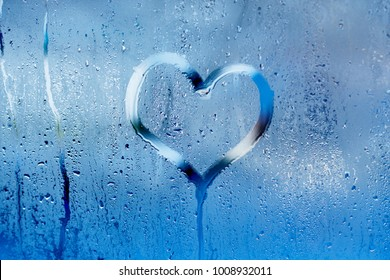 Hand draw a heart and drops of water on the glass. Condensation and raindrops on the window, shallow depth of field