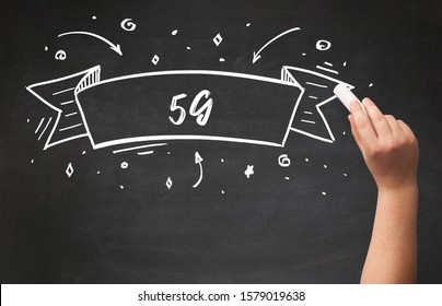 Hand drawing 5G abbreviation with white chalk on blackboard
