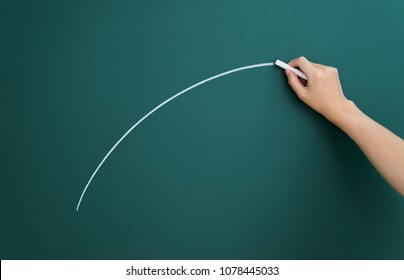 Hand drawing arc on blackboard