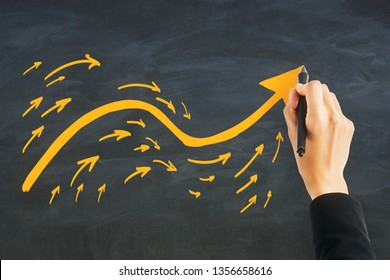 Hand drawing arrows on c halkboard wall background. Different direction and choice concept