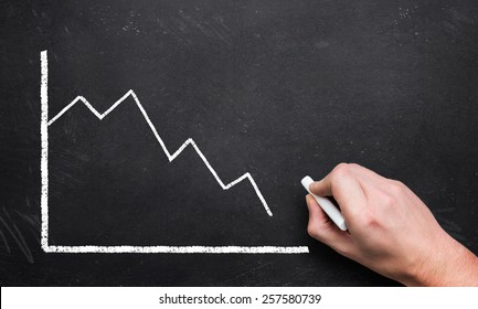 hand drawing a decreasing chart on a blackboard