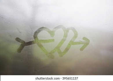 Hand drawing double heart with arrow on the wet window glass