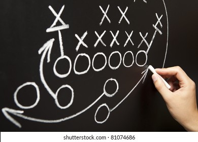 Hand drawing a game strategy with white chalk on a blackboard.