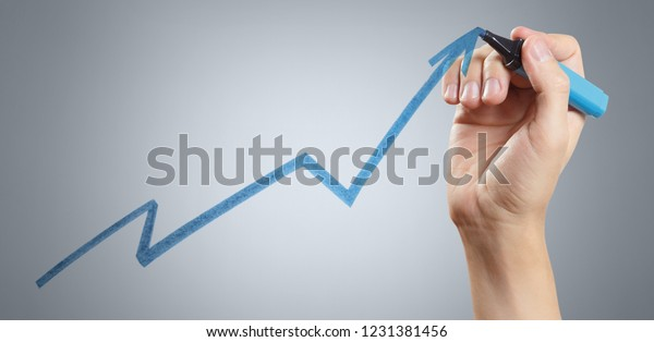 Hand drawing a growing graph using a blue marker on grey background
