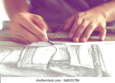hand drawing the human figure with a pencil, blurred movement.