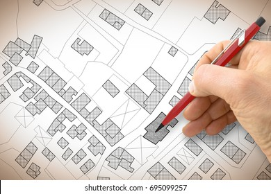 Hand drawing an imaginary cadastral map of territory with buildings and roads