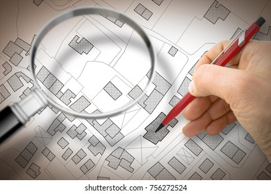 Hand drawing an imaginary cadastral map of territory with buildings and roads and magnifying glass