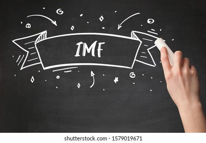 Hand drawing IMF abbreviation with white chalk on blackboard