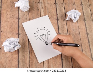 Hand drawing light bulb on a note pad. Concept for idea, creativity, imagination and perserverance