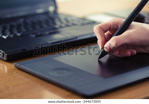 Hand is drawing on a digital graphic tablet with pen
