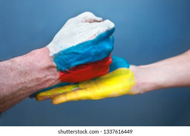 The hand with the drawing of the Russian flag hits on a hand with the drawing of the Ukrainian flag